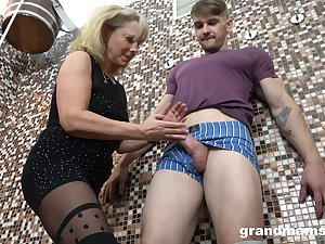 Dam gives a blowjob plus tugjob to young guy in an obstacle sauna
