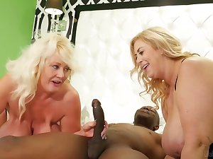 Lila Lovely and Kayla Kleevage are sharing a horny, glowering guy, during a most assuredly lucky threesome
